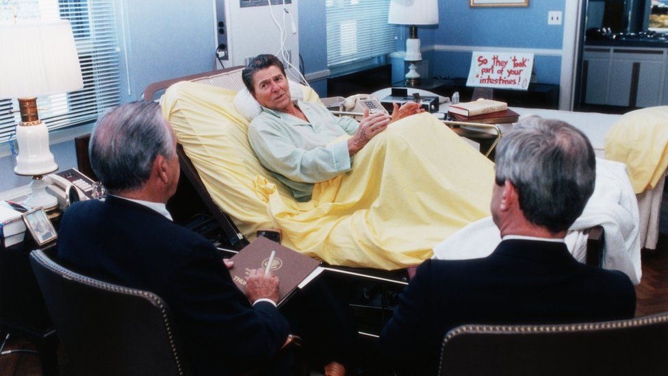 President Ronald Reagan holds a meeting with advisers while in the hospital for colon cancer surgery in 1985
