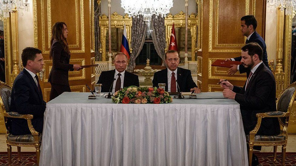 Russian Energy Minister Alexander Novak (L) and his Turkish counterpart Berat Albayrak (R) sign an agreement, flanked by Russian President Vladimir Putin (2nd L) and Turkish President Recep Tayyip Erdogan, before a press conference in Istanbul on October 10, 2016.