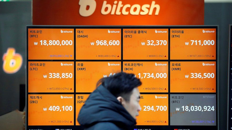 A man walks past an electric board showing exchange rates of various crypto-currencies including Bitcoin (top L) at a crypto-currencies exchange in Seoul, South Korea on 13 December 2017