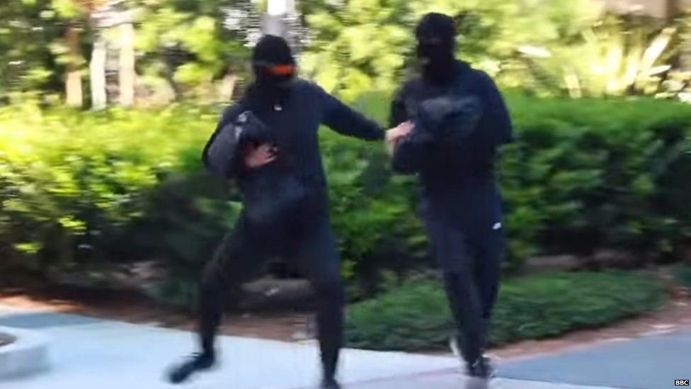 Alan and Alex Stokes pose as bank robbers in a YouTube video.