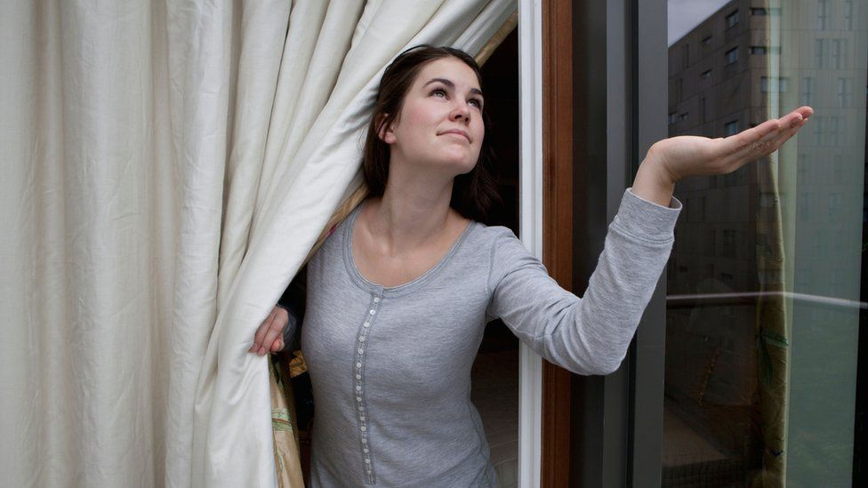 Woman checking out of a door to see if it is raining