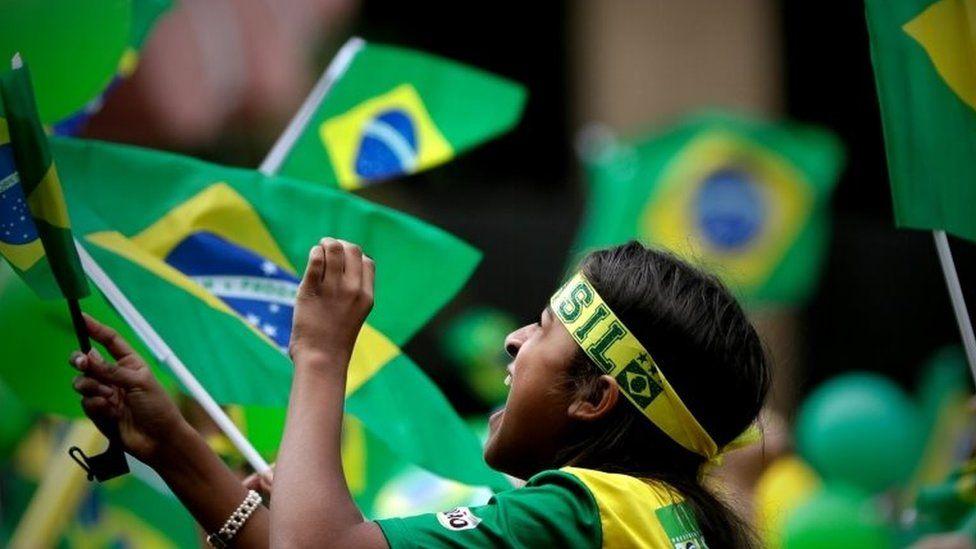 A supporter of Jair Bolsonaro waves a flag