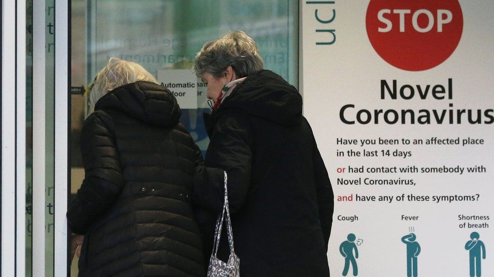 Two women walk past a sign providing guidance information about novel coronavirus (COVID-19) at one of the entrances to University College Hospital in London on March 5, 2020. - The number of confirmed cases of novel coronavirus COVID-19 in the UK rose to 85 on March 4, with fears over the outbreak delaying the global release of the new James Bond movie and causing lack of demand for air travel that has proved the final nail in the coffin for British regional airline Flybe which went into administration on March 5.