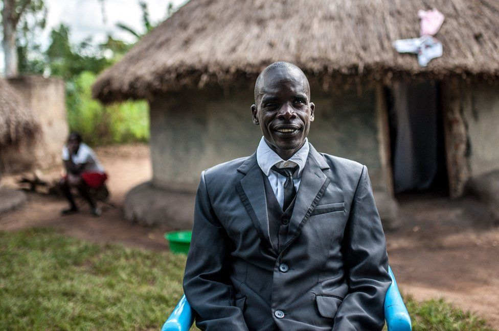 Simon Peter Otoyo sits outside his house in a blue chair