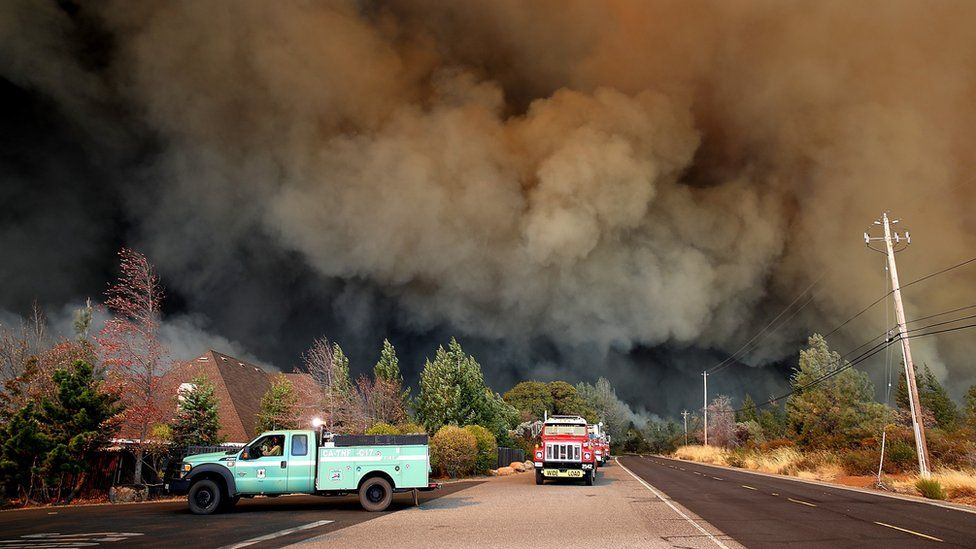 A plume of smoke rises above the Camp Fire as it moves through the area