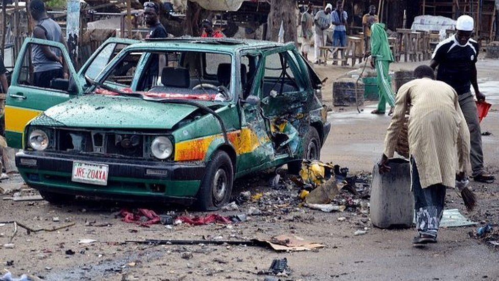 A man scouts for valuables beside a taxi damaged following an Improvised Explosive Devices (IED) at Gomboru market in Maiduguri, Borno State in northeastern Nigeria on July 31, 2015 detonated by a female suicide bomber who arrived on a taxi tricycle killings at least eight people and several other