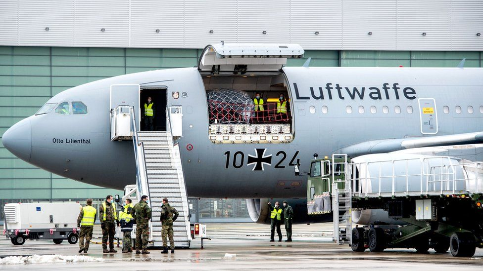 Staff of the German armed forces Bundeswehr stand around an Airbus A310-304 MRTT military transport plane of German armed forces Bundeswehr at the military airport in Wunstorf near Hanover, northwestern Germany, on February 3, 2021