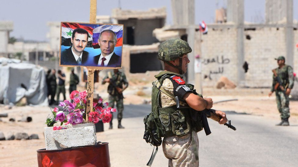 Members of Russian and Syrian forces stand guard near posters of Syrian President Bashar al-Assad and his Russia's Vladimir Putin on the eastern edge of Idlib province on 20 August 2018