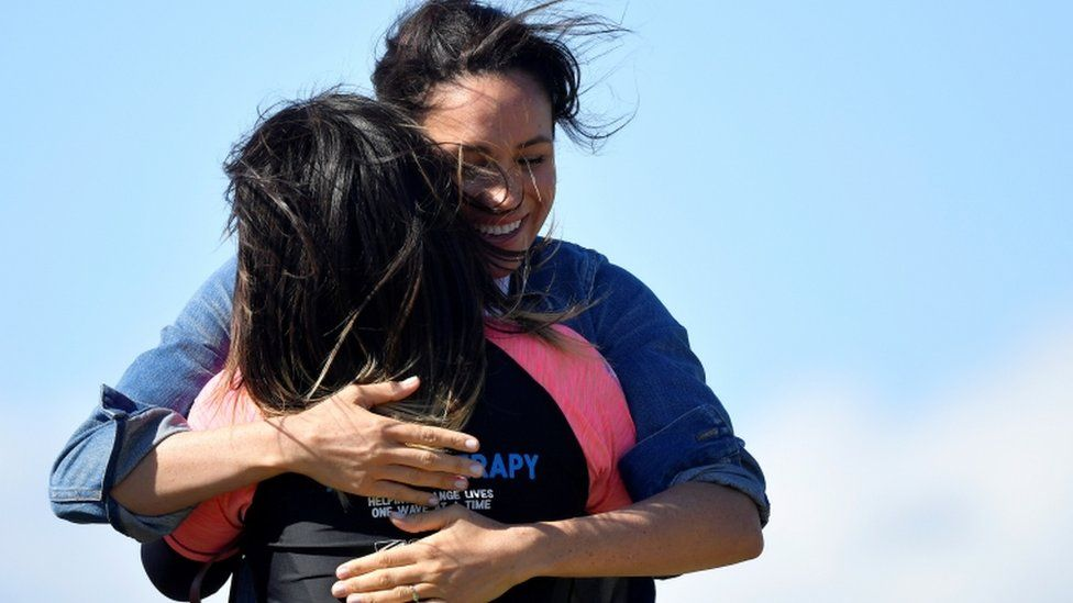 Meghan embraces a member of the NGO Waves for Change