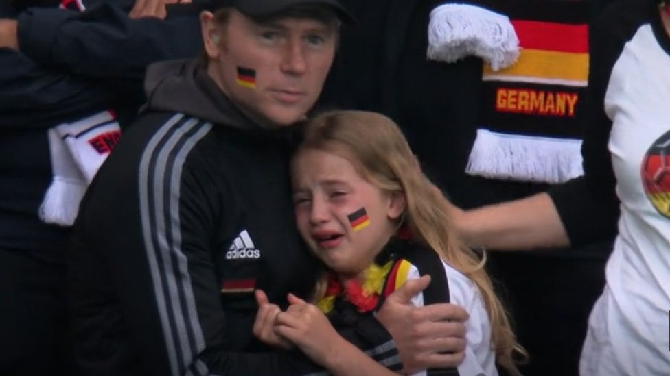 A young Germany fan crying while being hugged