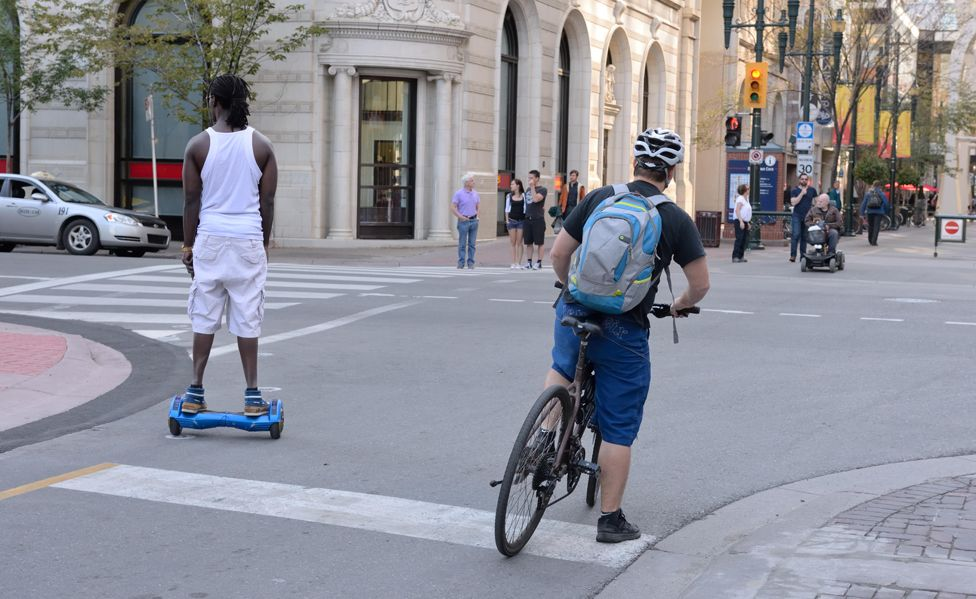 Man rides hoverboard on street in Calgary, Alberta