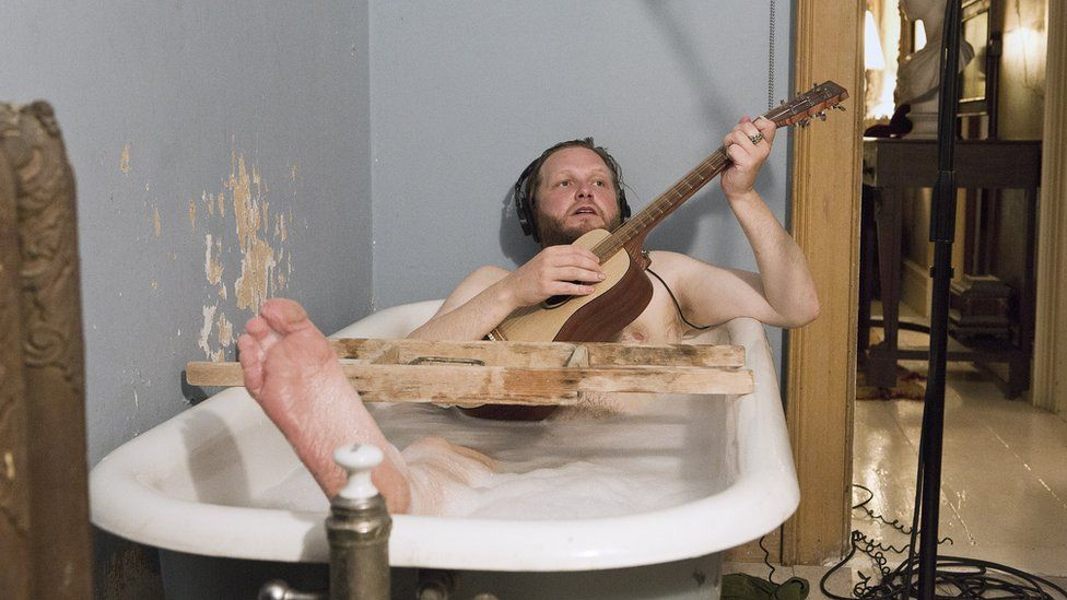 Photo of Ragnar Kjartansson playing guitar in the bath