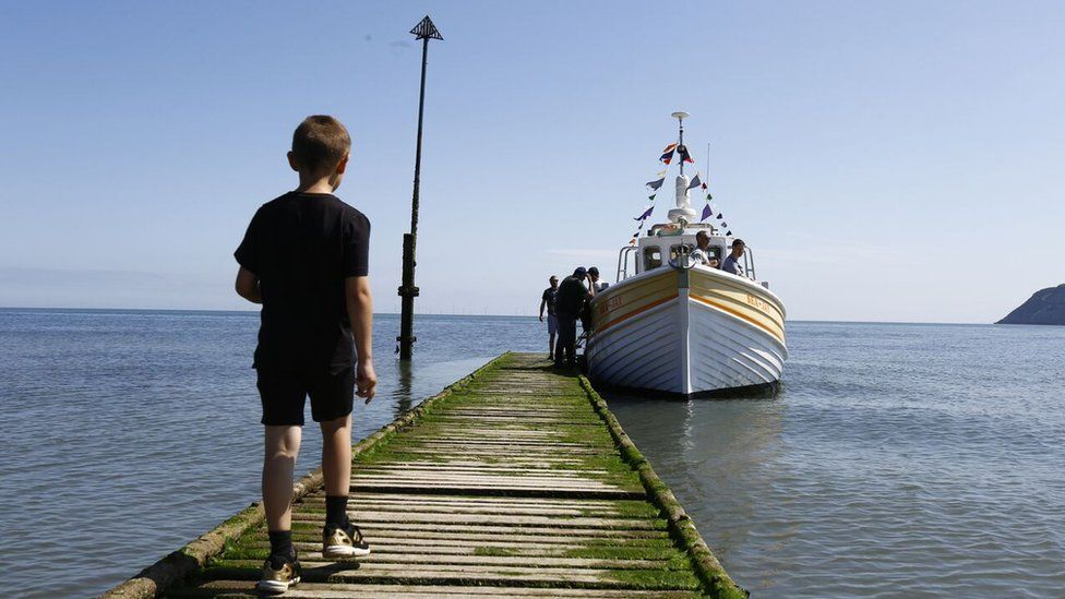 Boy walking out to a boat