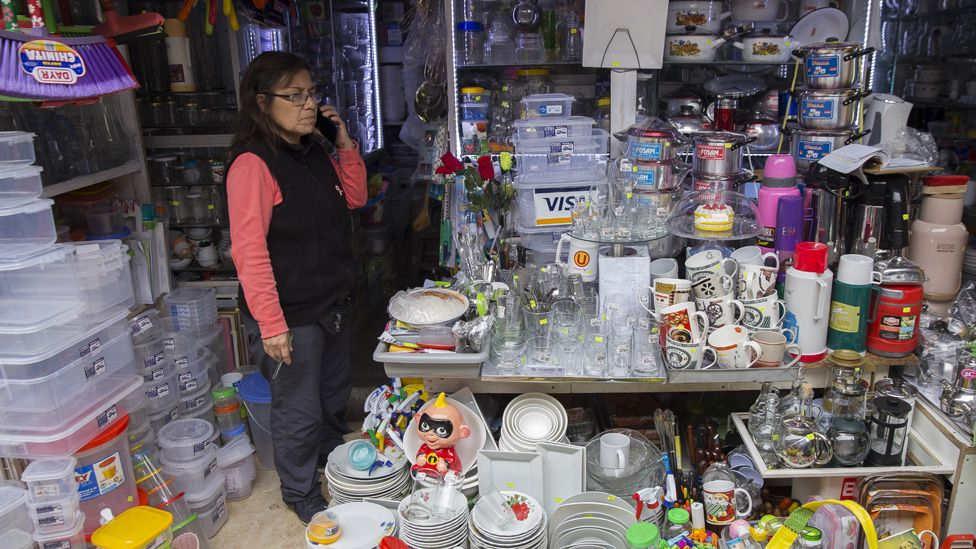 Peruvian merchant Alejandrina Bardales takes a inside her tiny market booth selling home good in Lima, Peru on July 19, 2019.