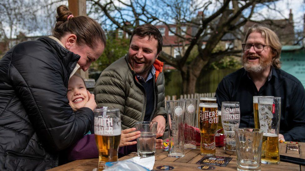 A group of people sitting at a pub garden table