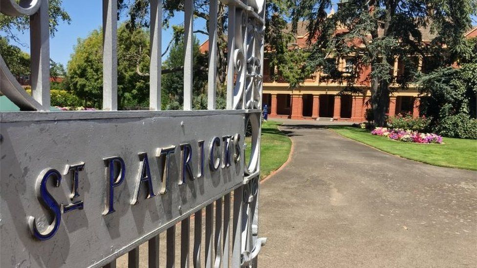 """A gate reads """"St Patrick's"""" in front of school grounds and a building"""