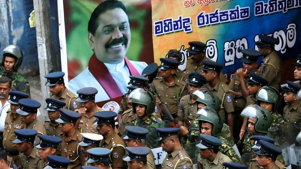 Members of Sri Lanka's Special Task Force and police officers stand alongside a poster of newly-appointed Prime Minister Mahinda Rajapaksa, 28 October 2018
