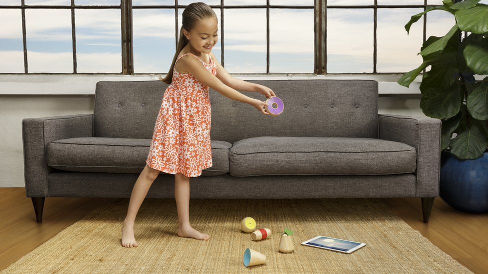 Young girl playing with wooden toys and tablet computer