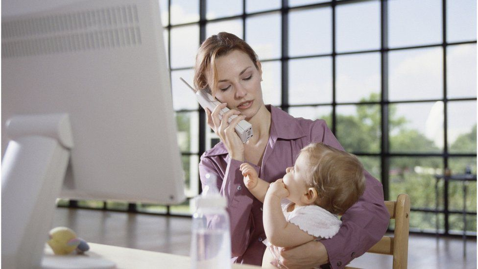 Woman holding a baby at her office desk