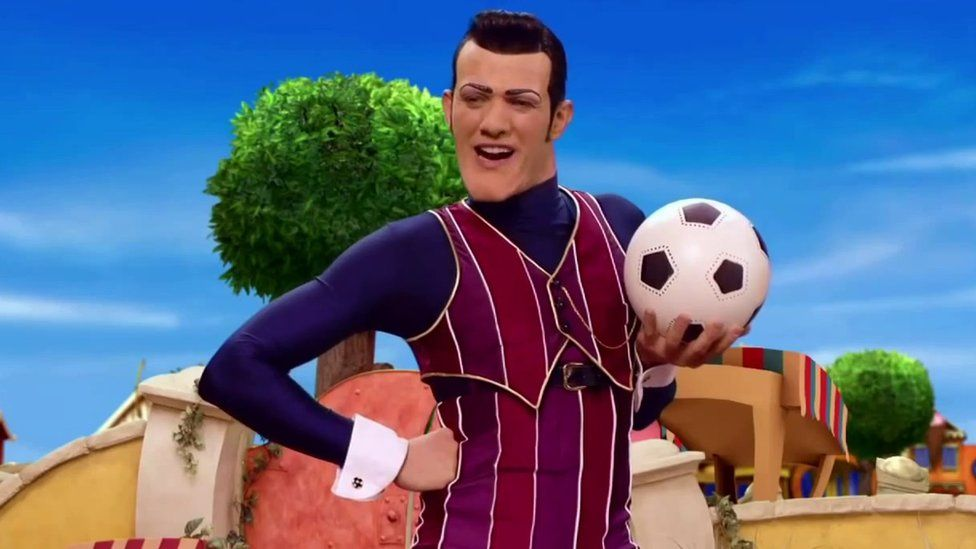 Robbie Rotten stands with a football