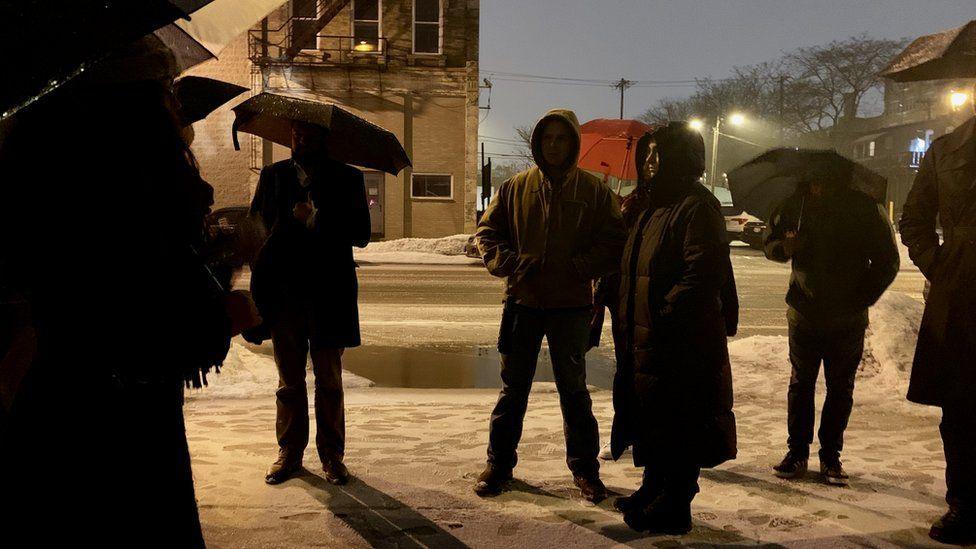 Turdaki insanlar bir ara sokakta şemsiye altında toplanırlar