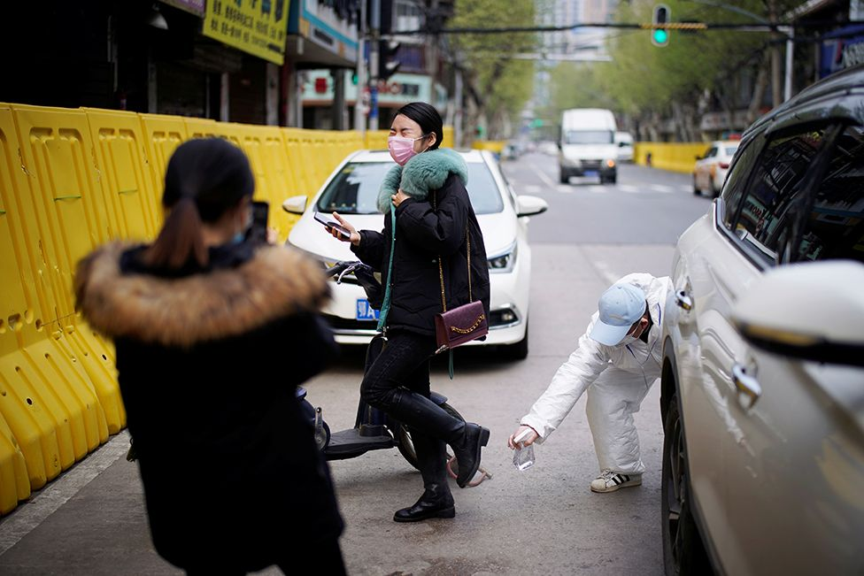 A person wearing a protective suit disinfects a woman's clothes on a street