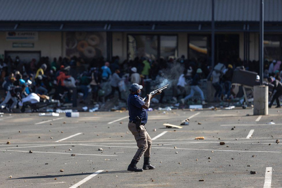 A member of the South African Police Services fires rubber bullets at rioters looting the Jabulani Mall in Soweto, southwest of Johannesburg, on 12 July 2021