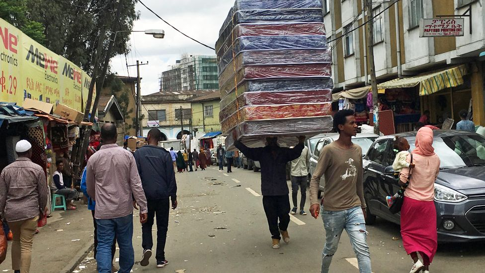 A man carrying mattresses on his head along a street in the Bole-Mikael neighbourhood of Addis Ababa in Ethiopoia