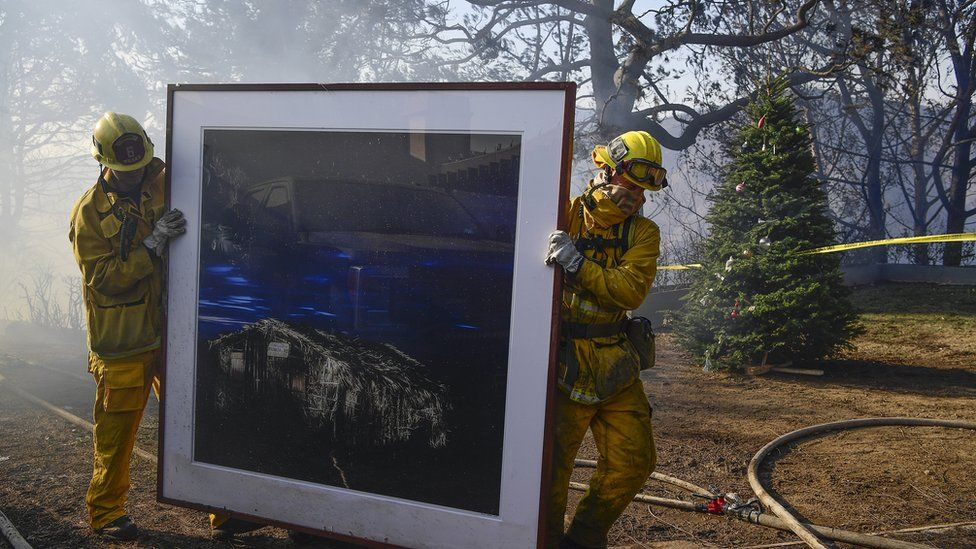 """Firefighters remove a painting as they continue to extinguish fires in a home during the """"Skirball Fire"""""""