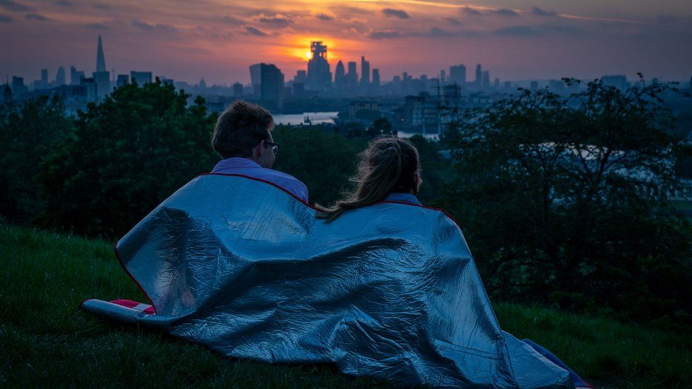 A couple wrapped up in a blanket as the sun sets from Greenwich Park, London, on Sunday