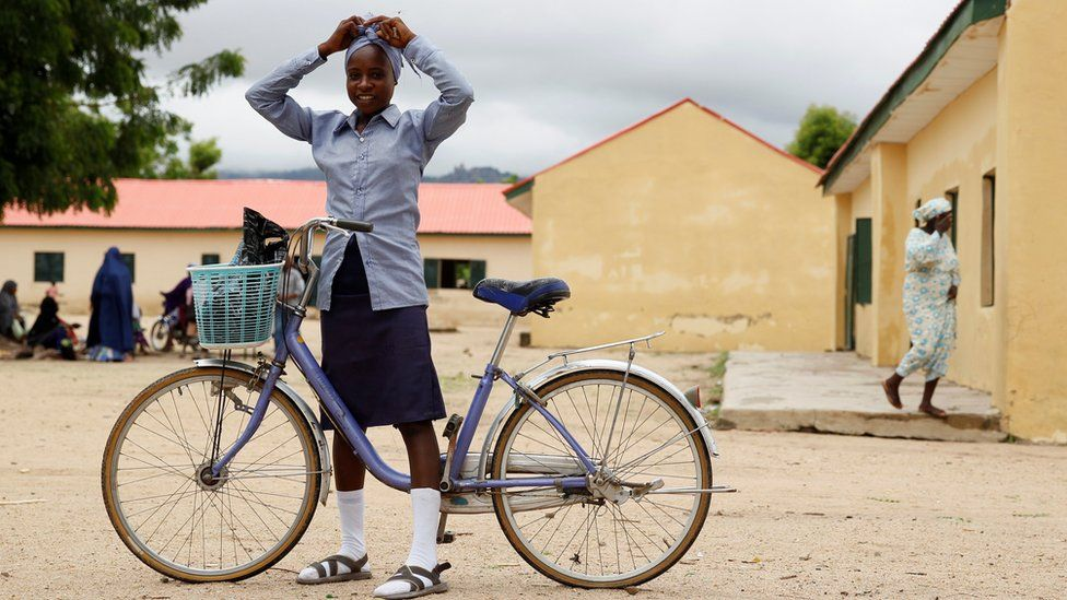 A student ties a scalf on her head as she prepares to ride a bicycle after the school hours at Hausari junior secondary school in Michika village, northeast Nigeria June 12, 2017