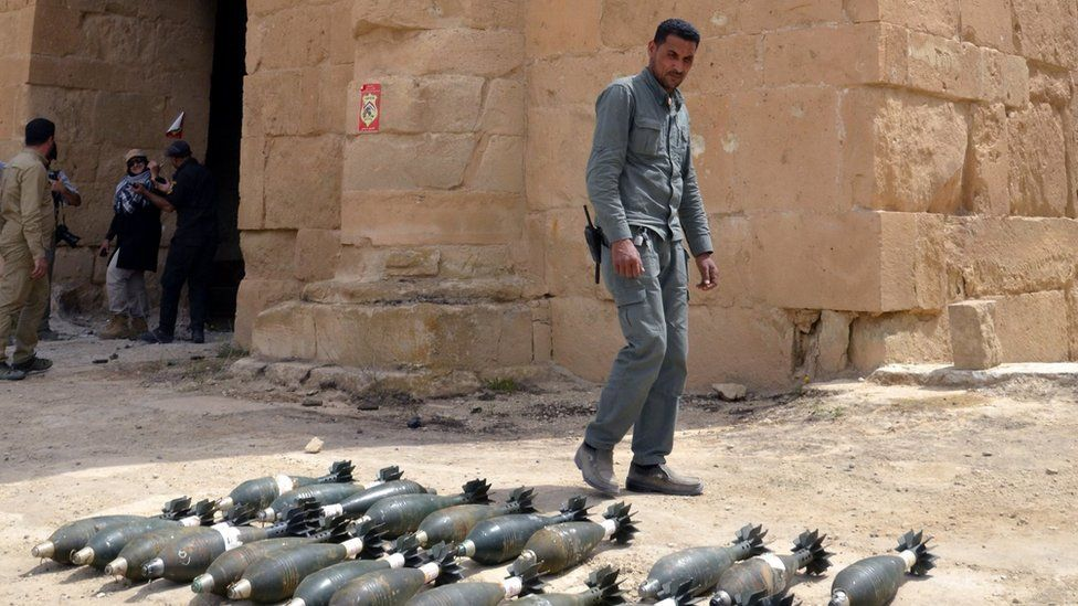 Member of the paramilitary Popular Mobilisation force inspects mortars found at the ancient city of Hatra in Iraq (28 April 2017)