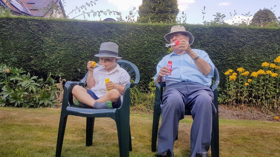 A man and a boy blowing bubbles