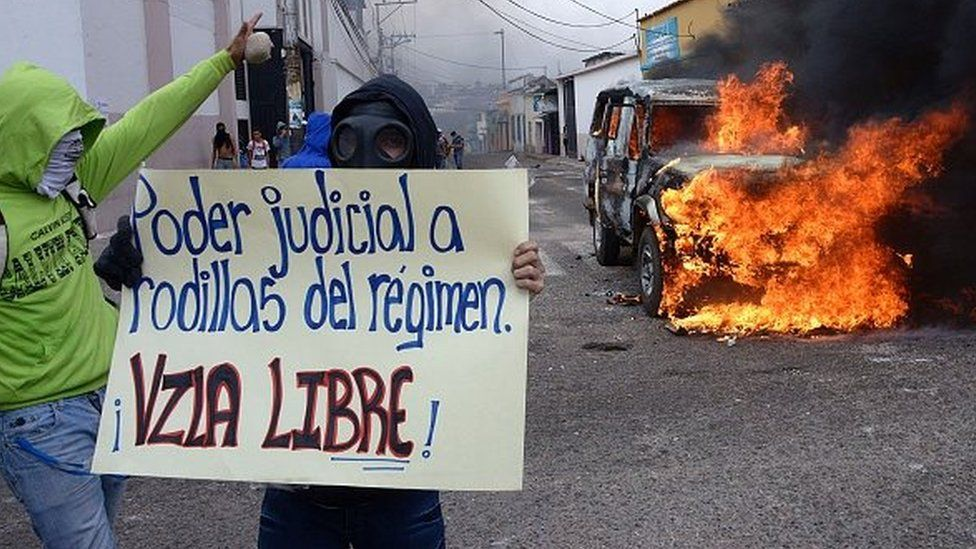 A student shows a poster reading 'Judiciary power is kneeling before the regime. Free Venezuela' during a protest against Venezuelan President Nicolas Maduro's government, in San Cristobal, Venezuela on March 3, 2016.