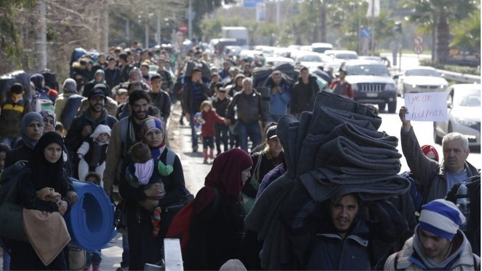 Hundreds of people leave the old international airport, which is used as a shelter for refugees and migrants, and walk along the seaside avenue in southern Athens, Friday, Feb. 26, 2016 as they try to find a solution to the closed borders