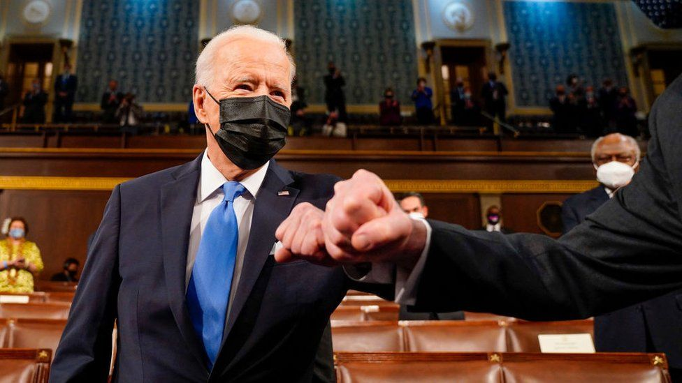 Joe Biden bumping elbows as he walks in to deliver his first speech to a joint session of Congress