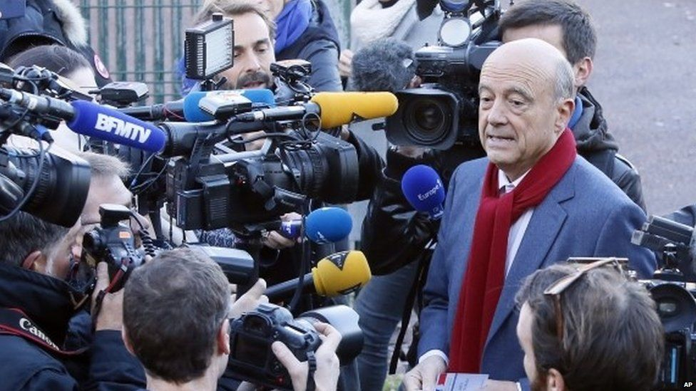 Former Prime Minister and Bordeaux's Mayor Alain Juppe, centre right, a candidate for France's upcoming presidential primary election arrives to vote for the conservative primary election in Bordeaux.