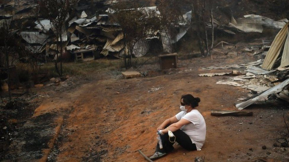 A woman takes a break while working to clean up the debris after a forest fire devastated Santa Olga, 240 kilometres south of Santiago, on January 26, 2017.