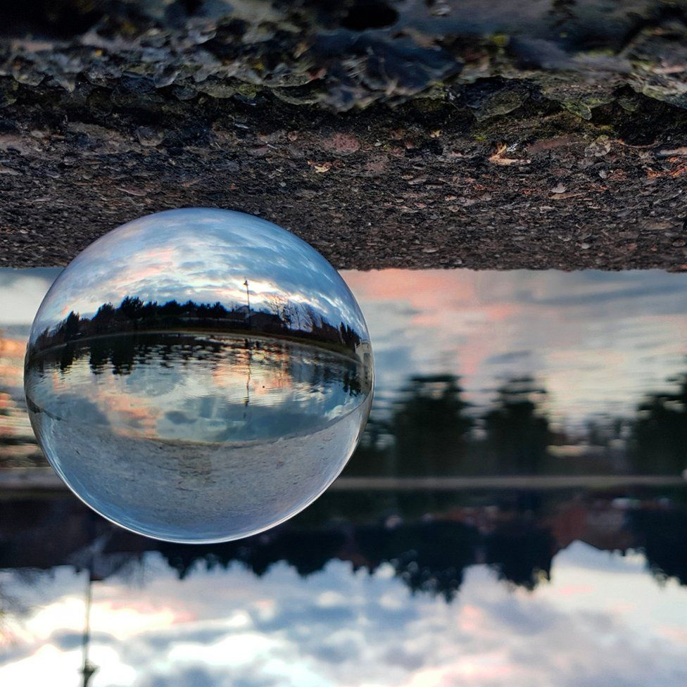 A sphere shaped clear ball showing sunset landscape against an up-side down background