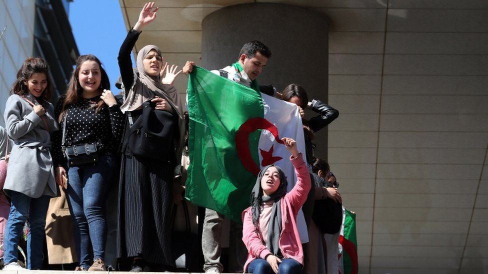 Algerian medical students hold up a flag at an anti-government protest in Algiers
