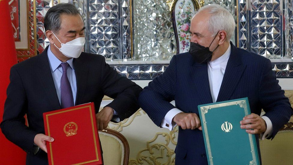 Chinese Foreign Minister Wang Yi and Iranian Foreign Minister Mohammad Javad Zarif bump elbows during the signing ceremony of a 25-year co-operation agreement in Tehran, Iran (27 March 2021)