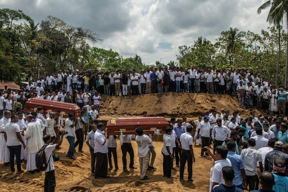 Coffins are carried to a grave during a mass funeral at St Sebastian's Church on 23 April in Negombo, Sri Lanka.