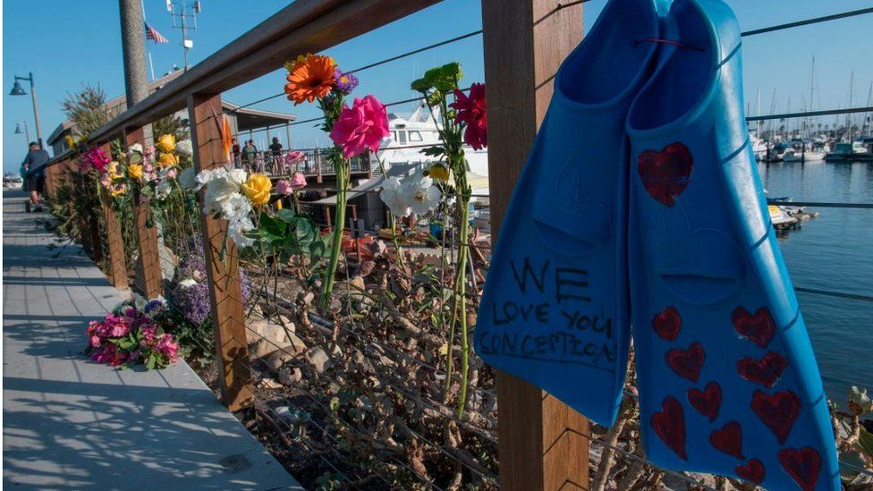 A pair of diving fins and flowers at a memorial wall near the Truth Aquatics moorings where the boat that burned and sank off the Santa Cruz islands early in the morning, was based in Santa Barbara, California
