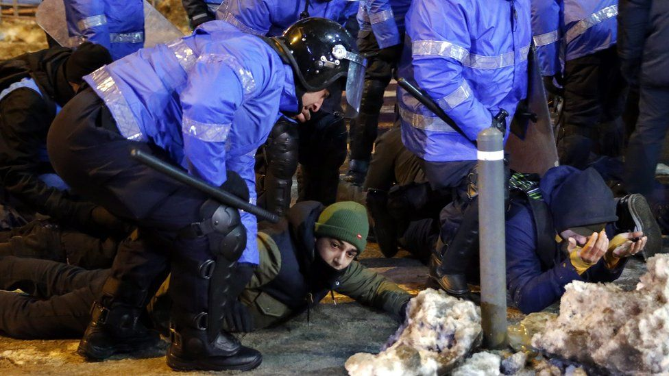Young protesters lay on the pavement with the hands on their head after being arrested by the riot police at the end of a protest rally in front of government headquarters in Bucharest, Romania