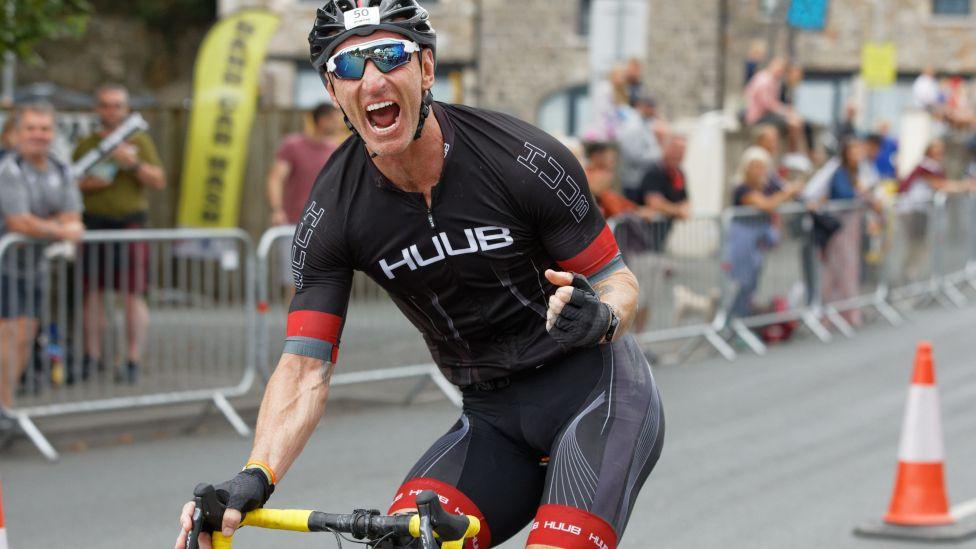 Gareth Thomas cheers to crowds at the Ironman Triathlon