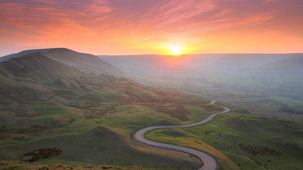 A photo of a sunset with a winding country road