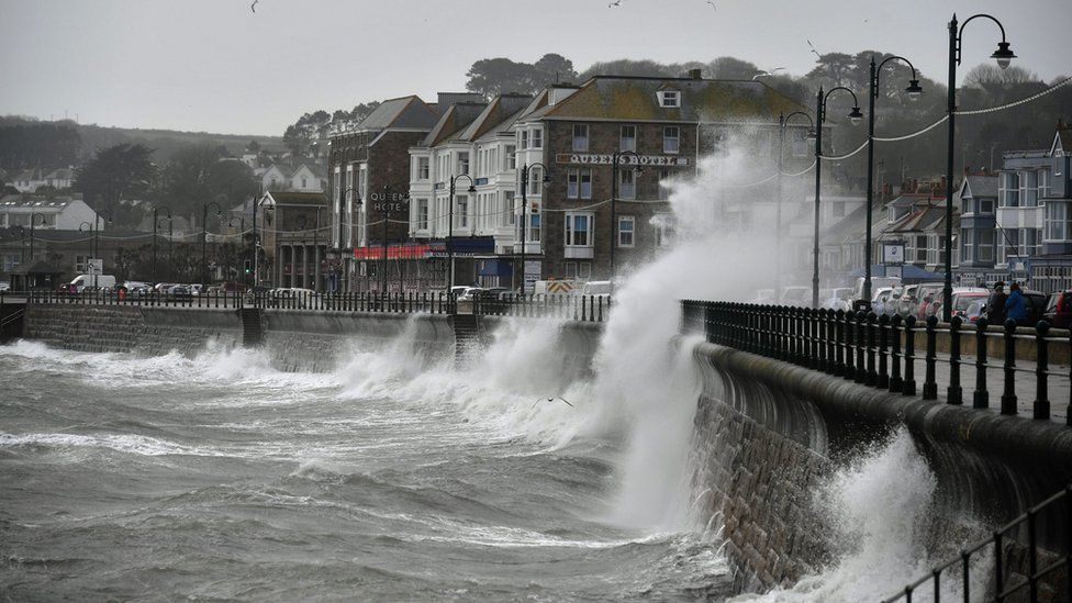 Waves crashing against the harbour wall in Penzance, Cornwall