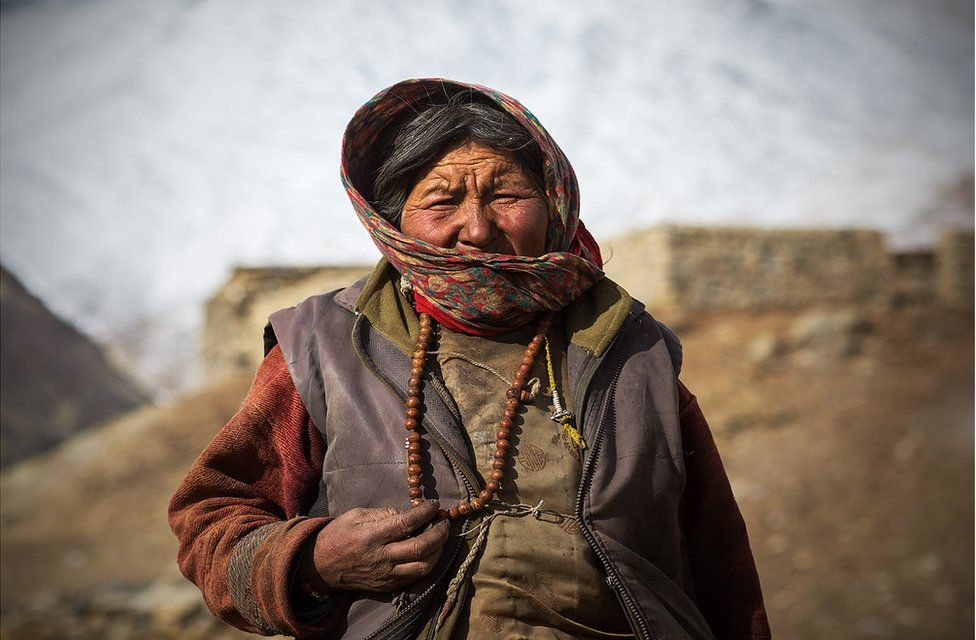 A woman stands wrapped up in many layers of clothing