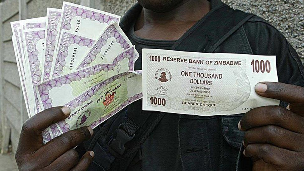 Harare resident holds up 1,000 and 50,000 dollar notes because of inflation, in 2006