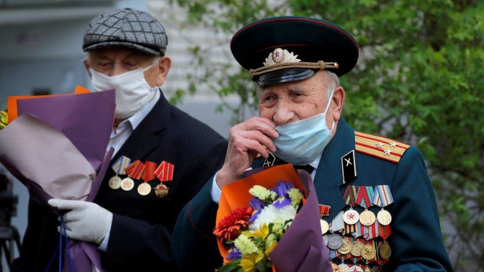 Belarusian veterans Pyotr Vorobyov and Pavel Eroshenko cover their faces with protective masks as they listen to a military band